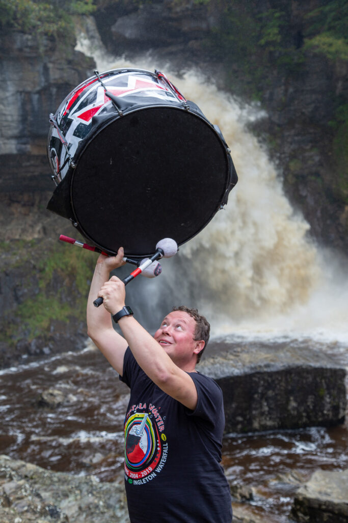 A drummer olding a bass drum in the air in front of a waterfall