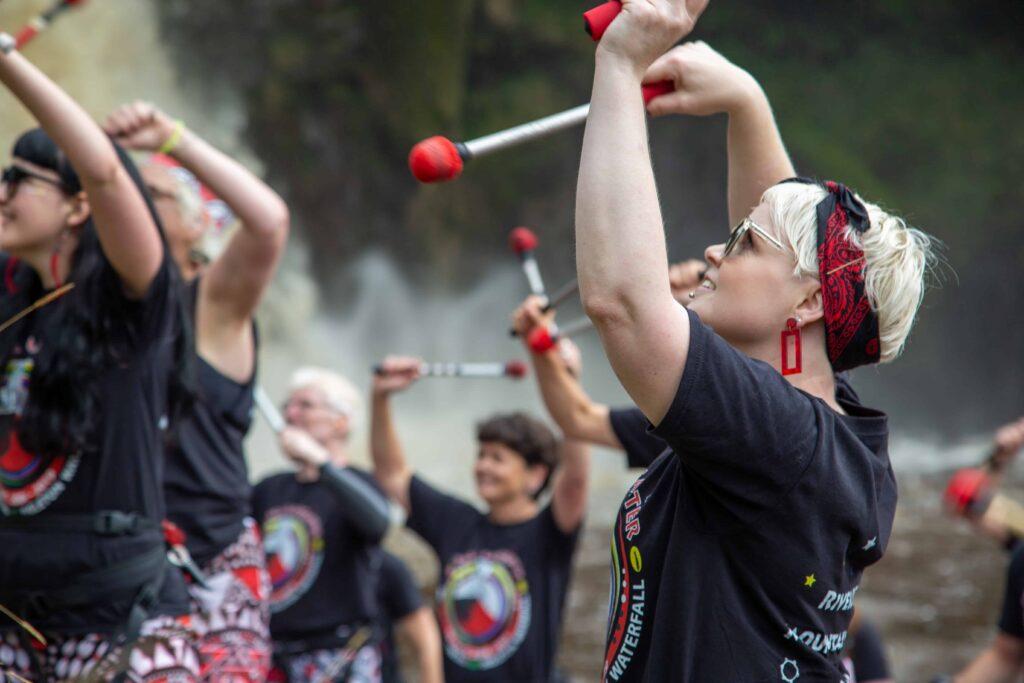 Batala Lancaster drummers in front of Ingleton waterfall