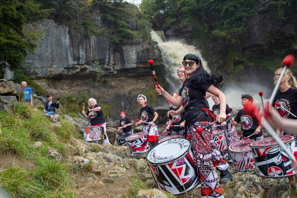 Batala Lancaster drummers in Ingleton waterfall